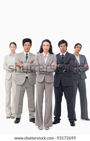 Serious businessteam standing with arms folded against a white background