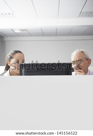 Serious businesswoman and businessman looking at computer in cubicle - stock photo