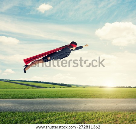 serious businesswoman dressed as a superhero in red mask and cloak flying at outdoor over beautiful landscape background - stock photo