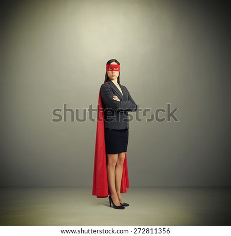 serious businesswoman dressed as a superhero in red mask and cloak over dark grey background - stock photo