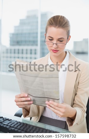 Serious businesswoman in bright office reading newspaper - stock photo