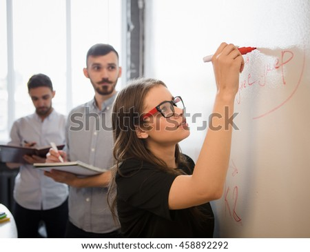 Serious businesswoman in glasses drawing diagrams or tables on whiteboard. Beautiful lady performing in board room in office interior.
