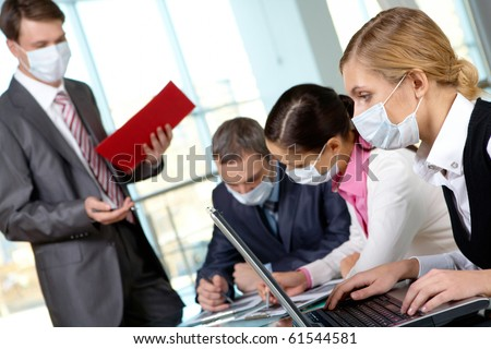 Serious businesswoman in protective mask looking at screen of laptop in working environment - stock photo