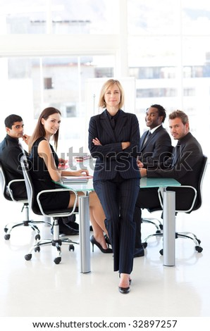 Serious businesswoman looking at the camera with folded arms in a meeting