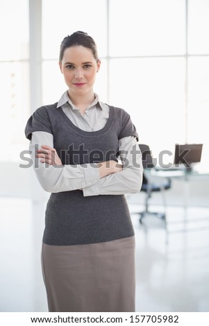 Serious businesswoman posing in bright office - stock photo