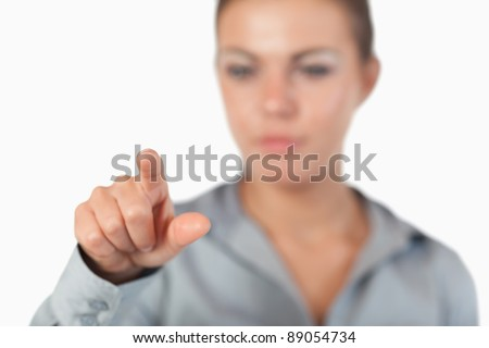 Serious businesswoman pressing an invisible key with the camera focus on her hand - stock photo