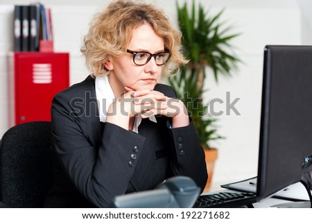 Serious businesswoman sitting with hands on chin - stock photo