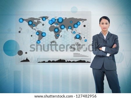 Serious businesswoman standing with a digital world map and graphs - stock photo