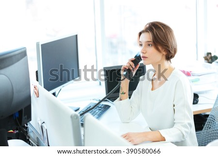Serious businesswoman talking on the phone in office
