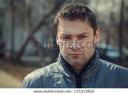 Serious casual man looking outdoor background. Closeup portrait - stock photo