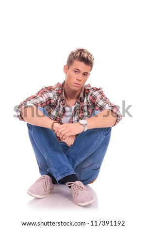 serious casual young man looking into the camera while sitting cross legged on the floor