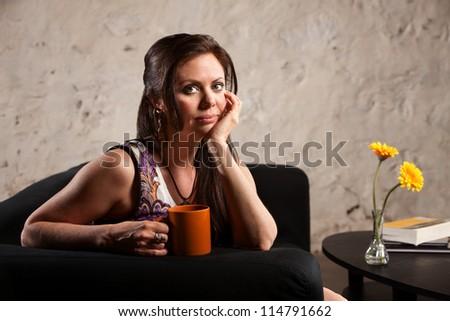 Serious Caucasian brunette female sitting indoors and holding mug - stock photo
