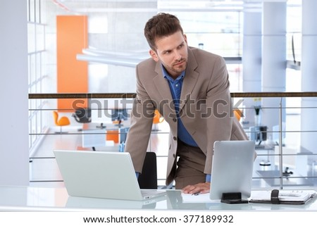 Serious caucasian businessman working with laptop and tablet at startup office desk, upstairs. Determined, standing, leaning on table, in the business. - stock photo