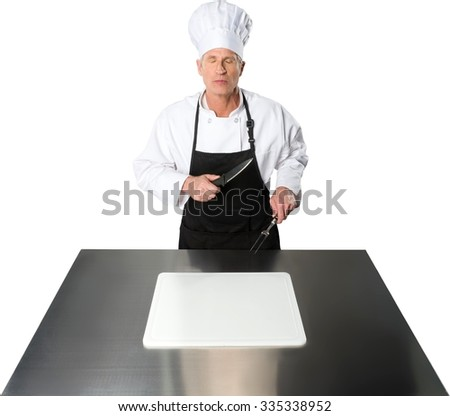 Serious Caucasian Chef  in uniform holding a knife and a two tined fork while standing behind a metal table with a cutting board - stock photo