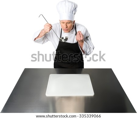 Serious Caucasian Chef  in uniform holding a ladle while standing behind a metallic table with a cutting board - Isolated - stock photo