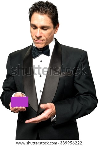 Serious Caucasian man with short black hair in a tuxedo holding business card - Isolated - stock photo