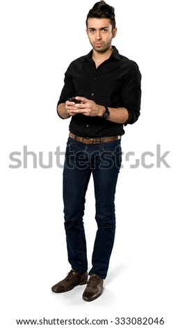 Serious Caucasian man with short black hair in casual outfit using mobile phone - Isolated