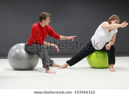 Serious caucasian pregnant woman exercising with personal trainer on large  stability balls in studio - stock photo