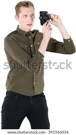 Serious Caucasian young man with short light blond hair in casual outfit using camera - Isolated - stock photo