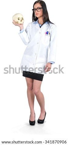 Serious Caucasian young woman with long dark brown hair in uniform holding skull - Isolated