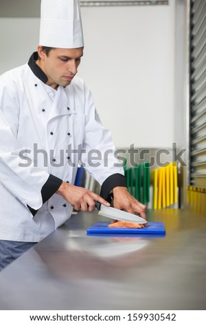 Serious chef cutting raw salmon with knife on blue cutting board in professional kitchen - stock photo