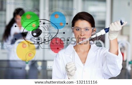 Serious chemist working with colourful cell diagram inteface in the lab - stock photo
