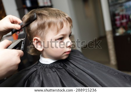 Serious child having a haircut at the barbershop