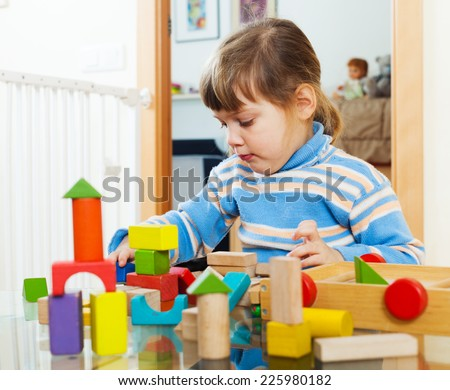 serious child playing with toys in home interior - stock photo