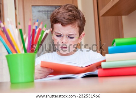 Serious child reading a book - stock photo