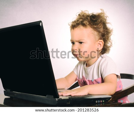 Serious child sitting and typing on the laptop computer.Selective focus on the child  - stock photo