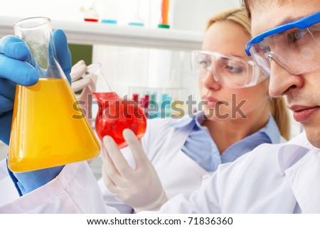 Serious clinician looking at flask with liquid on background of colleague - stock photo