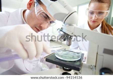 Serious clinician studying chemical element in laboratory with his assistant near by