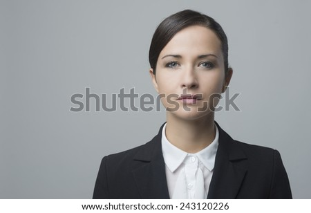 Serious confident businesswoman staring at camera and posing on gray background. - stock photo