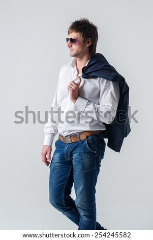 Serious confident cool attractive guy in jeans holding suit jacket on his shoulder looking away left side through sunglasses stands against wall. - stock photo