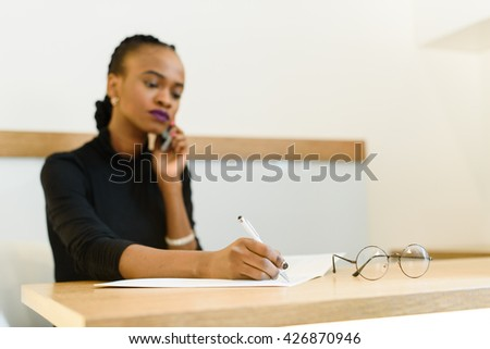 Serious confident young African or black American business woman on phone taking notes in office - stock photo