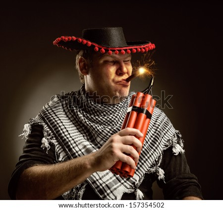 Serious cowboy mexican firing dynamite by cigar - stock photo