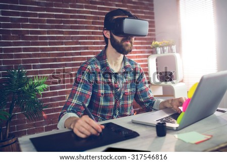 Serious creative businessman using 3D video glasses with laptop and graphic tablet at ofice - stock photo