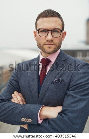 Serious determined young business man wearing glasses standing with folded arms looking at the camera with a pensive intense expression - stock photo