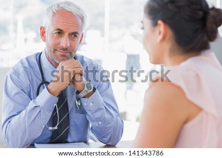 Serious doctor listening to patient explaining her painful in his office - stock photo
