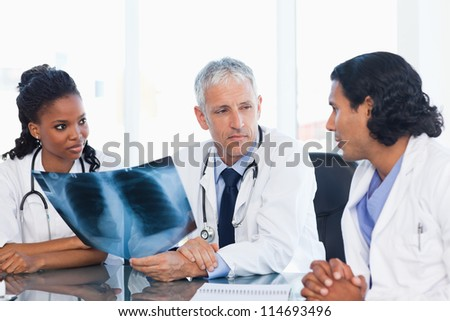 Serious doctor looking at an x-ray with two nurses - stock photo