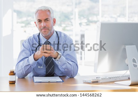 Serious doctor sitting at his desk and looking at camera - stock photo