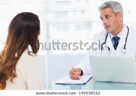 Serious doctor talking with his patient and writing on a notebook in medical office - stock photo