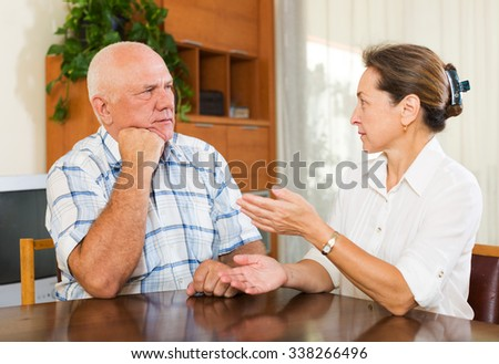 Serious elderly couple talking in home interior