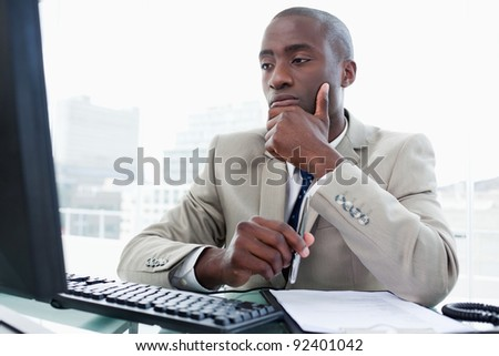 Serious entrepreneur while working with a computer in his office - stock photo