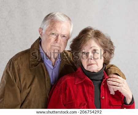 Serious European man and woman holding hands - stock photo