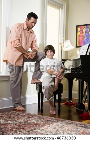 Serious father looking down at teenage son at home - stock photo