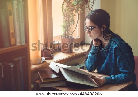 Serious female hipster student reading book, sit at the brown table in public university library. Young smart brunette young woman wearing glasses eyewear, jeans blue shirt. Education school concept. - stock photo