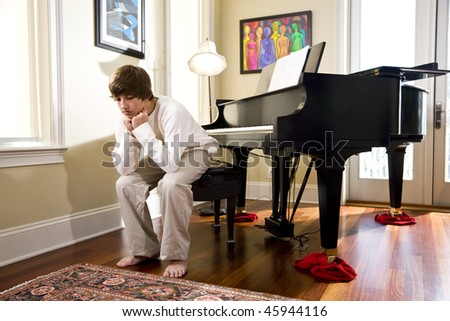 Serious fourteen year old teenage boy at home sitting on piano bench looking down - stock photo