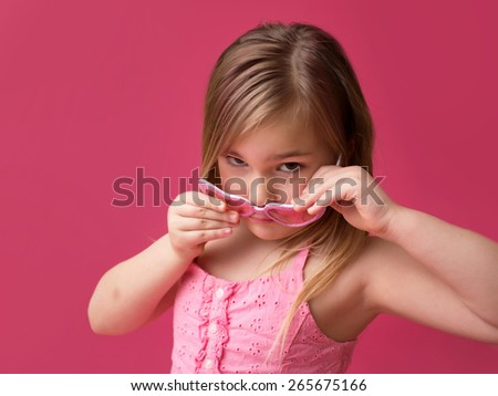 Serious girl in pink sunglasses looking at camera - stock photo