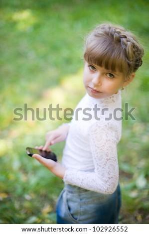 Serious girl uses touchscreen phone - stock photo